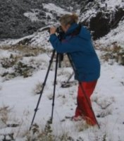 Theresa taking a photograph in the snow with a tripod